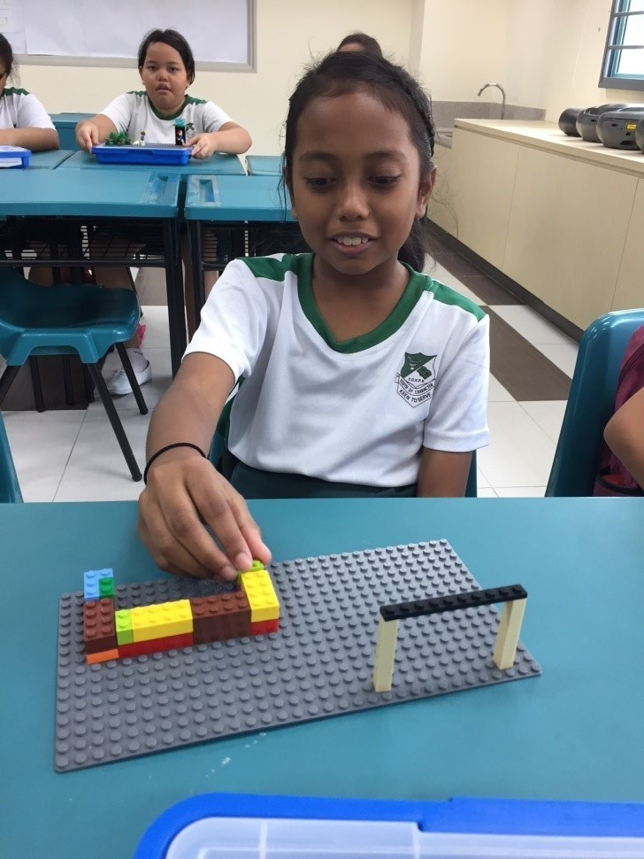 Malay students using LEGO blocks to build, expressing their learning of values.