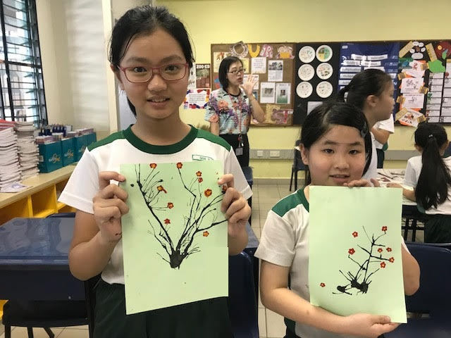 Students showcasing their plum blossom art piece created through blowing paint.