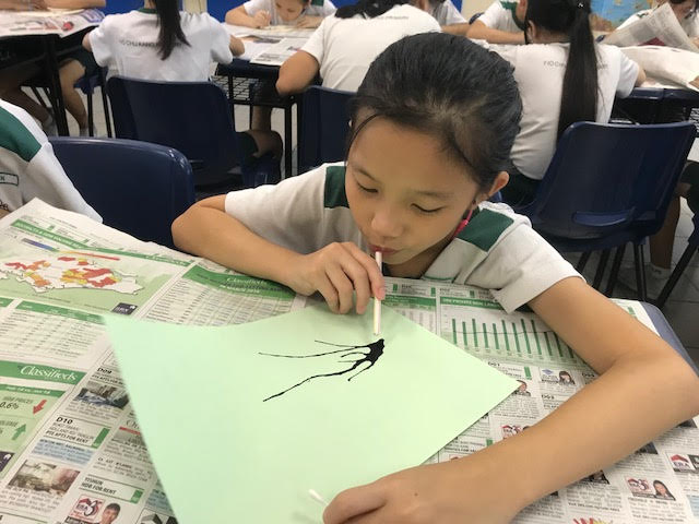 Student focusing on blowing the blot of paint to create a beautiful plum blossom tree.