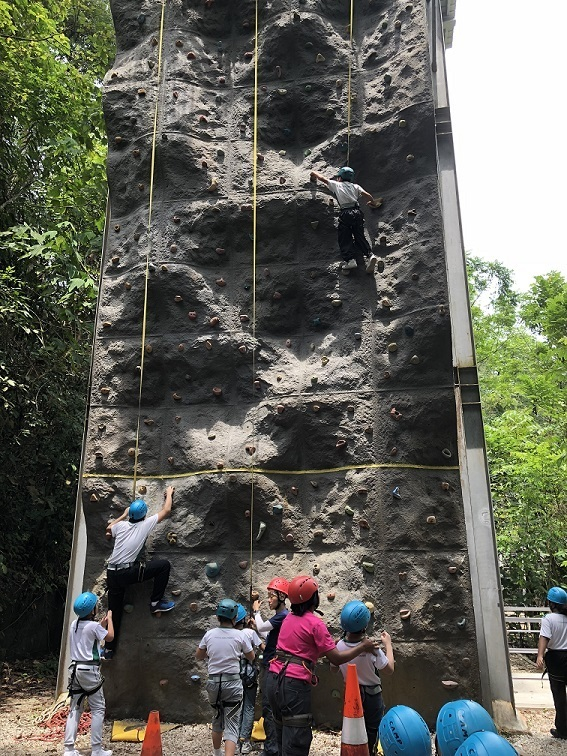 """There ain't no mountain too high for me"" - students trying their best to scale the peak of the rock wall."