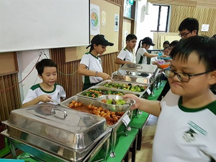 Students serving food to their fellow classmates during meal time.